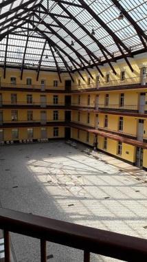 Le « Palais » devient une étonnante machine à habiter ensemble. Chacun des 3 pavillons s'organise autour d'une cour intérieure, recouverte d'une verrière avec son aération, sa diffusion de lumière naturelle ou artificielle, ses adductions d'eau, ses conduits de fumée, de ventilation, ses conduits et ses évacuations des déchets. Les appartements sont loués aux familles des employés de l'usine en fonction de leurs besoins, sur la base d'un prix au mètre carré, variable selon l'étage et l'exposition. Ici le bâtiment central aujourd'hui. Photo M.S.