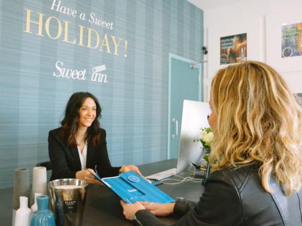 Un agent de relations accueillant une cliente dans leur bureau à Paris (c) Sweet Inn