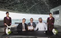 Peter Baumgartner, Chief Executive Officer d'Etihad Airways, Manuel Rabaté, directeur du Louvre Abu Dhabi, et Son Excellence Saif Saeed Ghobash, Director General of the Department of Culture & Tourism entourés de membres d'équipage Etihad Airways sous le dôme du Louvre Abu Dhabi – Photo officielle