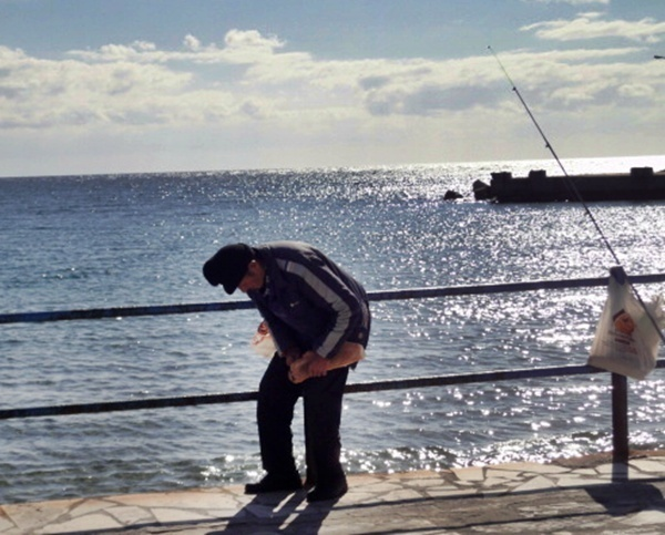 Un pêcheur vient de s'installer devant moi. Le bonnet de travers et la ligne pleine de nœuds.   Le léger tremblement de ses membres, sans doute inversement proportionnel avec la puissance du raki local, rend la pose des mini plombs et de l'hameçon aussi périlleuse que problématique...