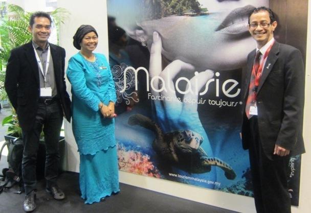 """L'équipe de l'office du tourisme de Malaisie devant l'affiche de sa campagne de communication : """" La Malaisie - Fascinante depuis toujours"""". DR"""