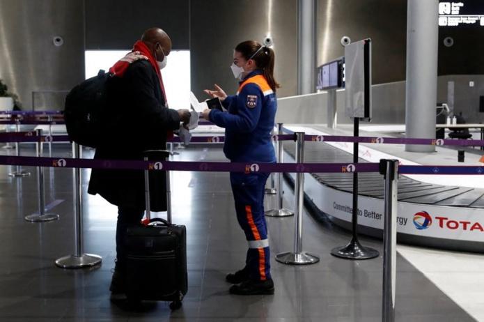 Une membre des services civiques vérifie les documents - dont une attestation de test au Covid négatif - d'un passager au départ de l'aéroport Roissy-Charles de Gaulle le 5 février 2021. Gonzalo Fuentes/AFP