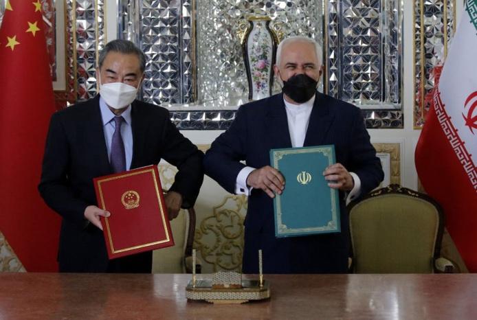 Le ministre iranien des Affaires étrangères, Mohammad Javad Zarif, et son homologue chinois, Wang Yi, posent après avoir signé un pacte de coopération stratégique à Téhéran, le 27 mars 2021. AFP