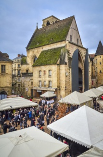 Market day in Sarlat. At the end is the ancient Sainte-Marie church, converted into an open air market, with its monumental door, a creation of the Jean Nouvel architect - DR