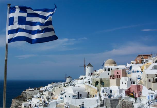 Le drapeau grec flottant au dessus de Santorin en Grèce. © zhukovandr - Fotolia.com