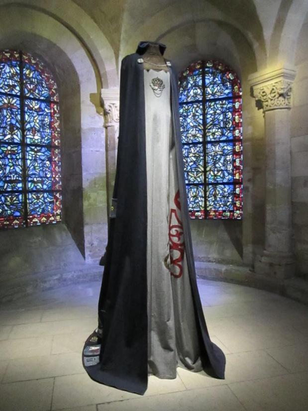Blanche de France, duchesse d'Orléans (1328 - 1393). Fille posthume du roi Charles IV  le Bel.  Sa naissance marque l'extinction des capétiens directs et l'arrivée sur le trône des Valois. Elle épouse en 1345 son cousin Philippe de Valois, duc d'Orléans, fils du roi Philippe VI.  Cotte en blouson bleu, surcot en denim gris, gorgerin en dentelle dorée. Cape en jean bleu et poches-logo en décor. Photo MS.