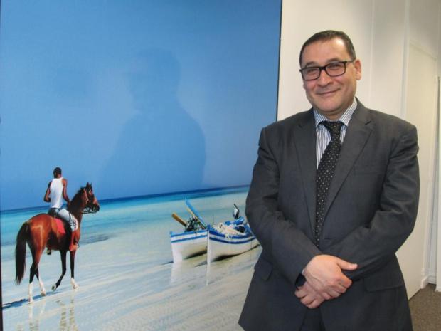 Abdellatif Hamam, directeur général de l'ONTT, devant une photo de Djerba dans les nouveaux bureaux de l'OT, avenue de l'Opéra à Paris - DR : M.S.