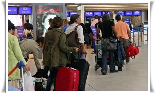 Une foutue queue digne du Guiness Book se hâtait lentement vers les comptoirs de «  dépose bagages »