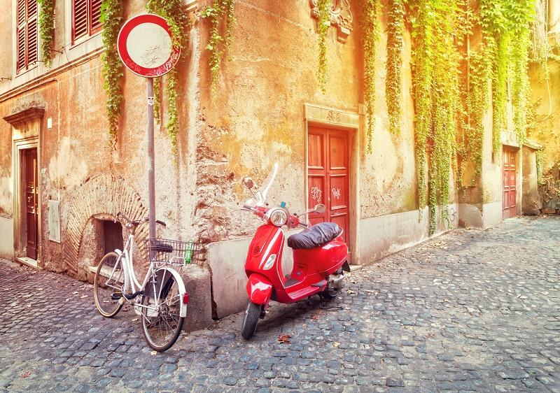 Une rue d'un vieille ville italienne avec un vélo et un fameux scooter © neirfy - Fotolia.com