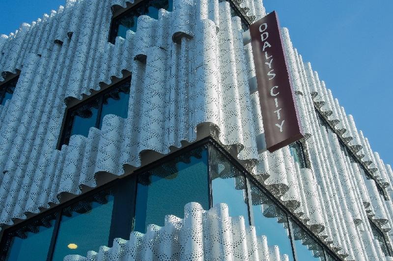 La façade est composée de panneaux métalliques réalisés sur mesure, formant un rideau ondulé, perforé, animant la grande façade sur la place Pouchet - Photo ODALYS
