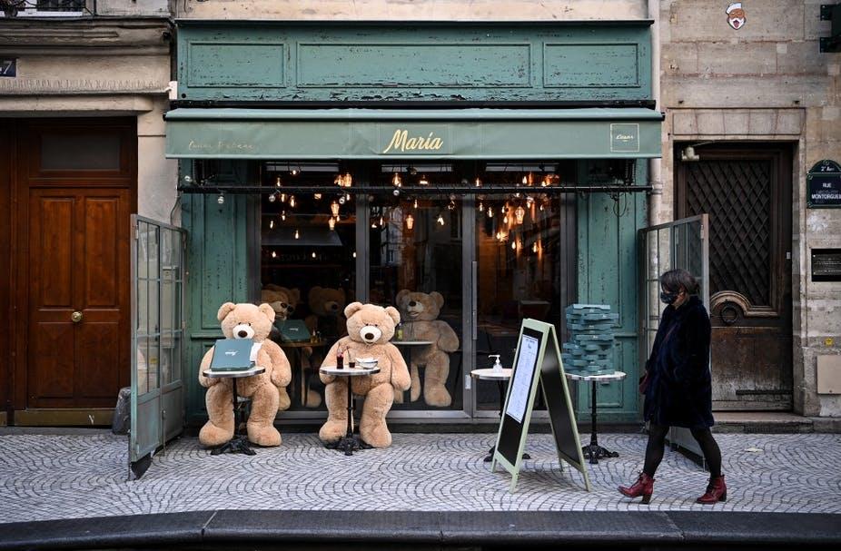 Devrons-nous recourir systématiquement à la technologie pour vaincre la crise sanitaire? Ici à Paris, terrasse d'un café ,le 23 mars où sont attablés les 'ours en peluche' de Philippe Labourel. Anne-Christine POUJOULAT / AFP