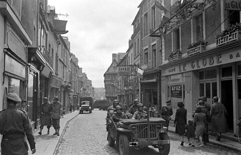 NARA/Soldats américains et britanniques dans la rue principale de Bayeux, qui n'a guère changé depuis la Seconde Guerre mondiale.