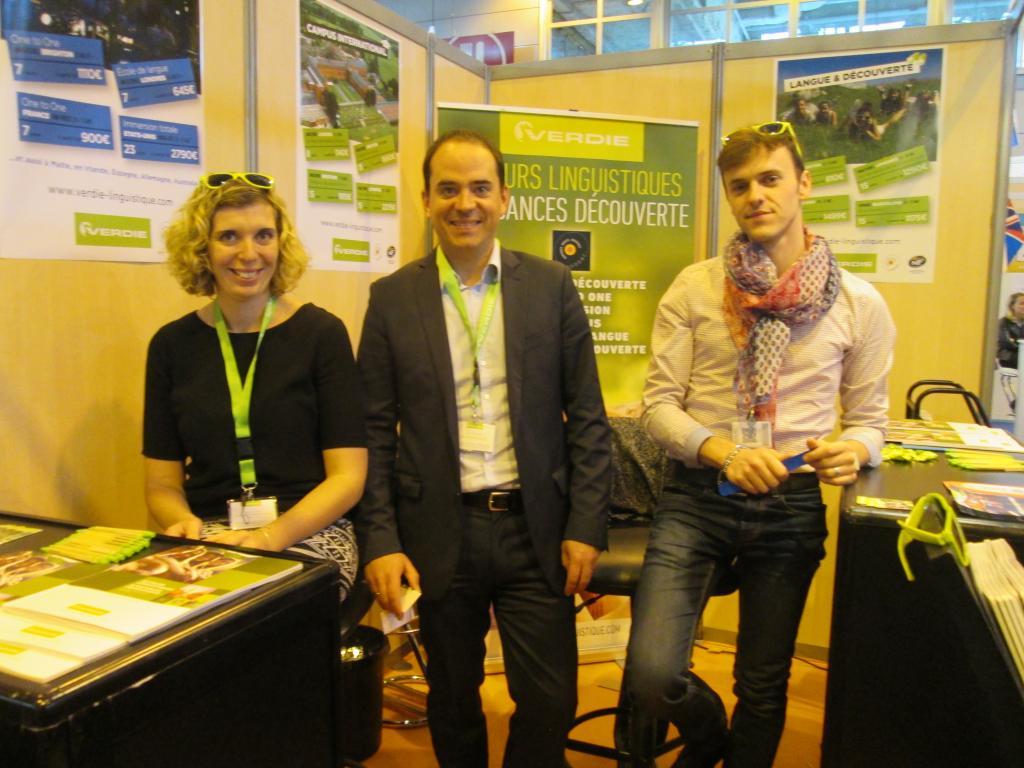 Sur l'espace des voyages linguistiques du Salon Mondial du Tourisme, Antoine Bretin directeur des ventes  entouré par deux collaborateurs venus de Rodez où siège l'entreprise. MS.